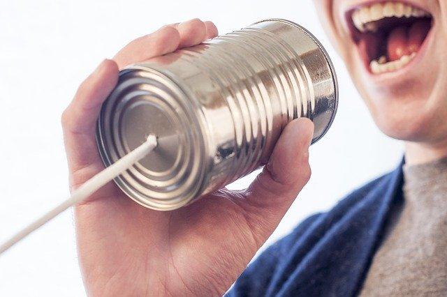 缶詰の糸電話に発言する男性