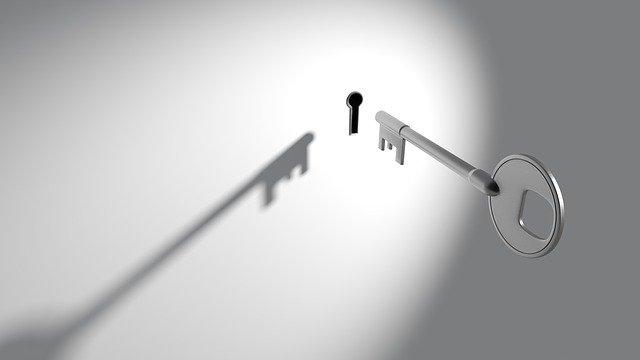 壁に空いた鍵穴に鍵を差す様子