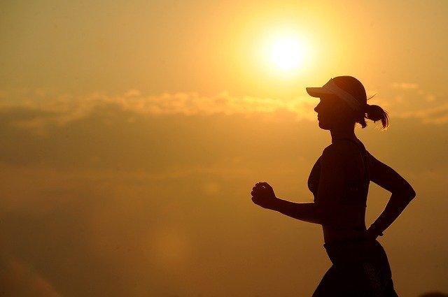 健康のために夕陽の中ジョギングしている女性