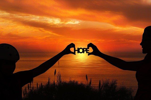 男女が夕日の前で『HOPE』の文字を持つ